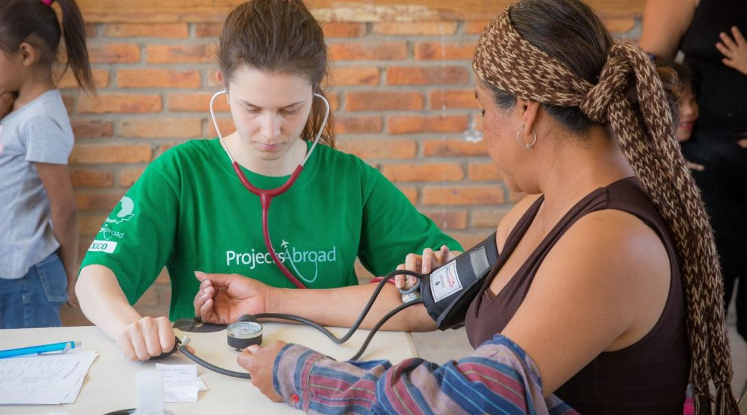 Projects Abroad volunteer measures the blood pressure of a local woman in Mexico